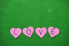 Pink hearts with the word love being arranged Stock Photography