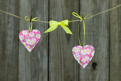 Pink hearts and yellow ribbon hanging on clothesline by rustic wooden background Stock Photos