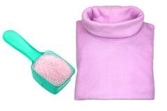 A pink heat retaining turtleneck shirt next to washing powder Stock Images