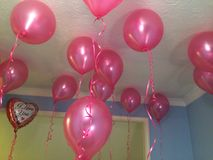 Pink helium balloons floating in a room with an I Love You heart shaped ballon in the corner very romantic Valentine's Day idea. Royalty Free Stock Photography