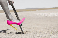 Pink high heel shoe and shovel digging in dirt. Concept filtered image of womans leg wearing pink high heel stiletto shoe and one hand on shovel, digging in Royalty Free Stock Photos