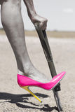 Pink high heel shoe and shovel digging in sand. Concept filtered image of female leg wearing pink high heel stiletto shoe and one hand on shovel, digging in Royalty Free Stock Photos
