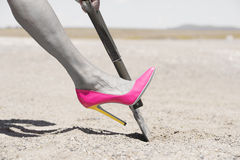 Pink high heel shovel digging in desert dirt. Concept filtered image of womans leg in pink high heel stiletto shoe and one hand on shovel, digging in remote Stock Photography