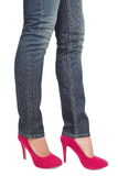 Pink high heels and jeans - woman legs. Woman in hot pink red high heels shoes and jeans. Fashion feet and legs closeup of lower half body isolated on white Royalty Free Stock Photography