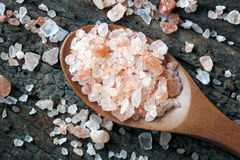 Pink Himalayan Rock Salt. Spoonful of pink Himalayan rock salt, over weathered timber Stock Image