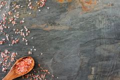 Pink Himalayan salt side scene. Top view on dark background. Royalty Free Stock Images