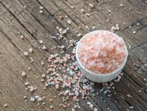 Pink Himalayan salt in white salt shaker on wooden background. Healthy spice closeup royalty free stock photo