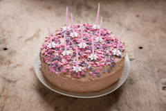 Pink, homemade birthday cake with heart candies and flower candles Stock Photo