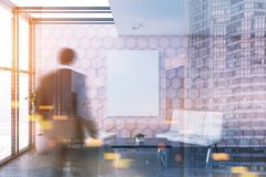 Pink honeycomb office lounge, poster, man blur. Businessman in a pink honeycomb wall pattern office lounge with loft windows, a coffee table, and two white sofas Stock Photo