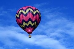 Pink Hot Air Balloon. A pink hot air balloon floats in a cloudy blue sky Stock Photos