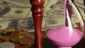 Pink hourglass. Close up. Pink hourglass, sand flowing through an hourglass, glass clock standing on the dollar bills, sand pink, time is sand, close up stock video