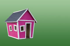 Pink House. Pink wooden play house against green background Stock Image
