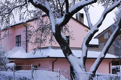 Pink house behind a snowy fence Royalty Free Stock Photo