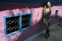 Pink house and a girl. Girl with long plaits standing at pink house Royalty Free Stock Photo