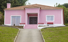 Pink house with vehicle entrance way in out and garden Royalty Free Stock Photography