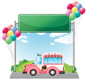 A pink ice cream bus near an empty green board Royalty Free Stock Photo
