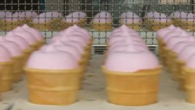 Pink fruity and vanilla ice cream in a waffle cup. Pink ice cream close up. Ice-cream production line. Ice cream filling in cups, cones stock video footage