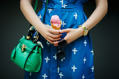 Pink Ice cream in the girl hand. Girl with green bag and glasses holding a pink ice cream cone Stock Photos