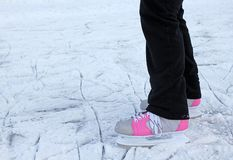 Winter background - pink ice skates. Winter background - legs of an ice skater on winter ice royalty free stock photography
