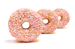 Pink Iced Doughnut. Abstract covered in sprinkles isolated against white background stock images