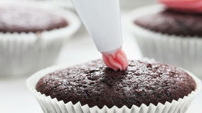 Pink Icing. Decoration of chocolate cupcake with pink icing stock footage