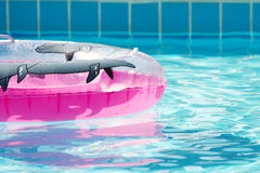 Pink inflatable round tube. In swimming pool stock images