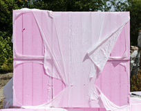 Pink insulating boards wrapped. Bundle of pink insulating boards wrapped with disrupted white plastic royalty free stock image