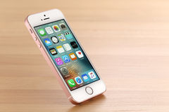 Pink iPhone SE. Koszalin, Poland – July 15, 2016: Pink iPhone SE. Devices displaying the applications on the home screen. The iPhone SE is smart phone stock image