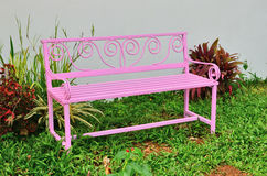 Pink iron seat beside the wall. Pink iron seat in the garden beside the wall Stock Photos