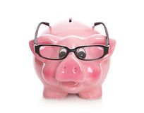 Pink isolated piggy bank with glasses on white. Royalty Free Stock Images