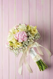 Pink and ivory wedding bouquet on pink wooden background, gift for holidays and celebration Royalty Free Stock Images
