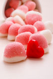 Pink jellies or marshmallows with sugar on table. Sweet food candy. Pink jellies or marshmallows with sugar in white bowl on wooden table decorated with red royalty free stock image