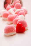 Pink jellies or marshmallows with sugar on table. Sweet food candy. Pink jellies or marshmallows with sugar in white bowl on wooden table decorated with red stock photos
