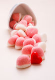 Pink jellies or marshmallows with sugar on table. Sweet food candy. Pink jellies or marshmallows with sugar in white bowl on wooden table decorated with red royalty free stock images