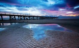 Pink Jetty Sunset. Beautiful pink sunset at the beach royalty free stock photo