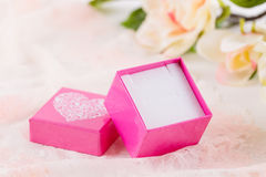 Pink jewelry gift box. Empty pink jewelry gift box on lace background with flowers Stock Photography