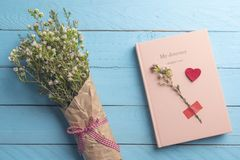 Pink journal and flowers bouquet. Flat lay on blue background. Pink notebook and beautiful spring flowers bouquet on a blue wooden table. Romantic flat lay image royalty free stock images