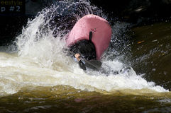 A pink kayak flips as a paddler does his stunts. Royalty Free Stock Images