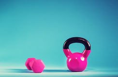 Pink kettlebell and dumbbell on a blue background. Pink kettlebell and dumbbell on a blue gradient background Stock Images