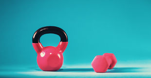Pink kettlebell and dumbbell on a blue background. Pink kettlebell and dumbbell on a blue gradient background Royalty Free Stock Photos