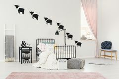 Pink kid`s bedroom interior. Patterned pouf next to kid`s bed with white knit blanket in pink bedroom interior with ladder and sheep stickers on the wall stock photo