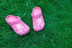 Pink kid`s slippers on green lawn. Copy space. Top view, located at side of frame. Horizontal. Concept of unity with nature. stock photo