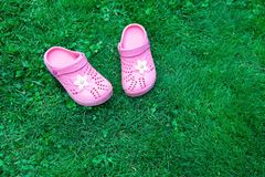 Pink kid`s slippers on green lawn. Copy space. Top view, located at side of frame. Horizontal. Concept of unity with nature. stock image