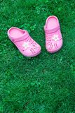 Pink kid`s slippers on green lawn. Top view, located on top of the frame. Vertical. Concept of unity with nature. stock images