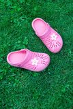Pink kid`s slippers on green lawn. Top view, in the middle of frame. Vertical. Concept of vacation with children. stock photos