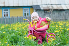 Pink kids trike with yellow wheels and little hunkering toddler girl sitting behind vehicle Royalty Free Stock Image