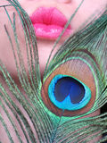 Pink Kiss. Pink lips with a peacock feather royalty free stock photography