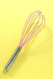 Pink kitchen whisk on yellow background Stock Image