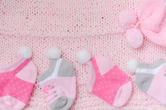Pink knit hat and socks gift set for a newborn baby girl on knit Royalty Free Stock Photography