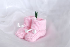 Pink knitted baby booties Stock Image